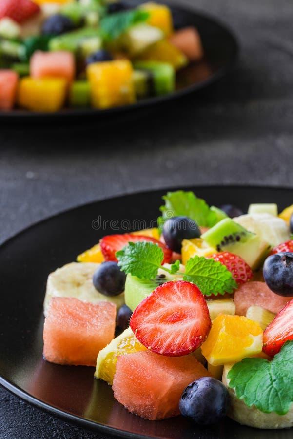Fresh fruit salad on dark background. Close up royalty free stock photo