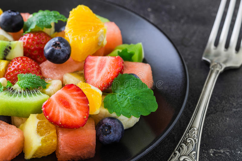 Fresh fruit salad on dark background. Close up royalty free stock photos