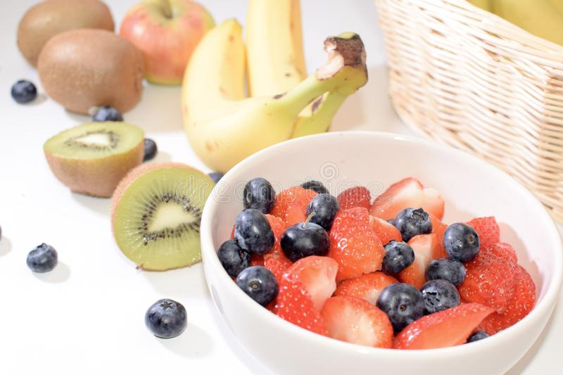 Fresh fruit, strawberries, berries, bananas, kiwis on a white background. Ingredients for a amoothie. Fresh strawberries, blueberries, bananas, kiwis on a white stock photography