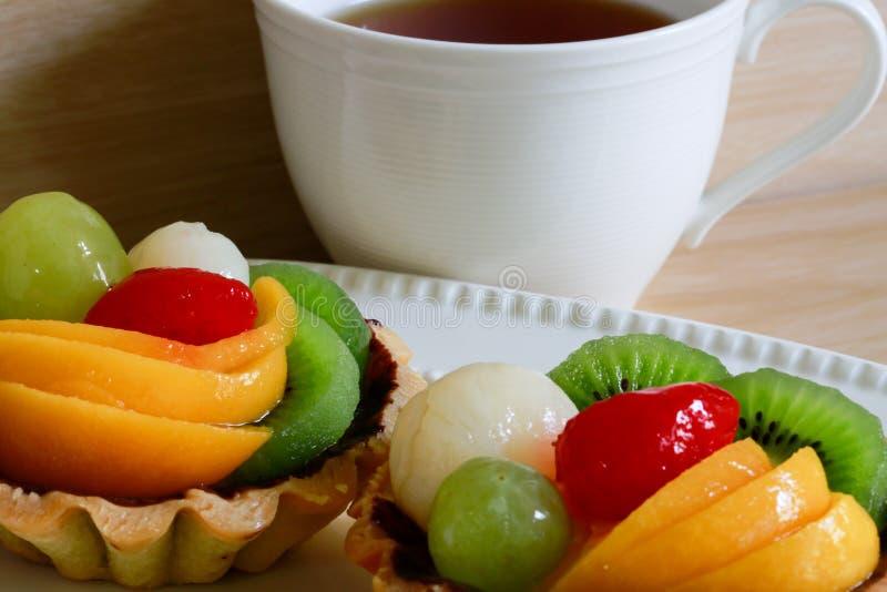 Fresh fruit tarts on wooden panel include kiwi, lychee,grapefruit, strawburry,peaches royalty free stock photography