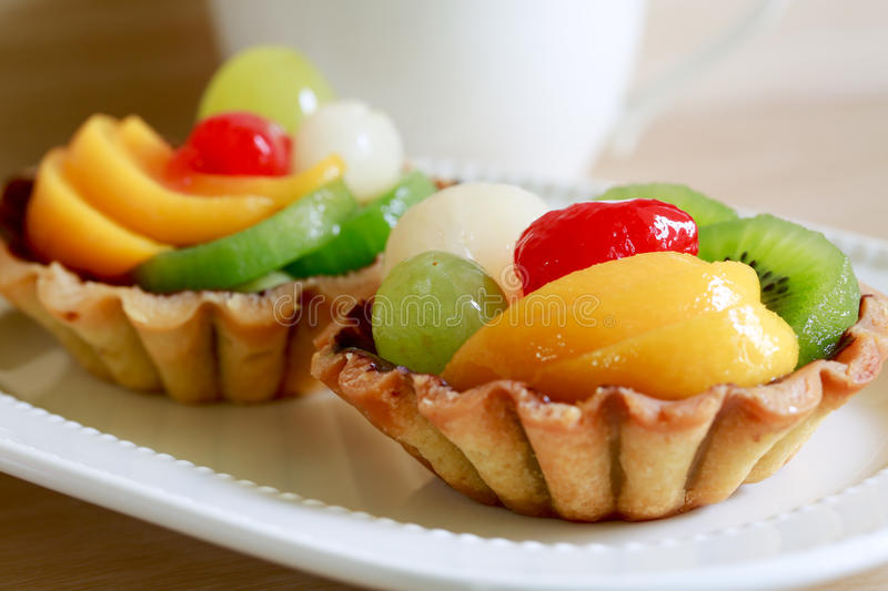 Fresh fruit tarts on wooden panel include kiwi, lychee,grapefruit, strawburry,peaches and a cup of herbal tea royalty free stock images