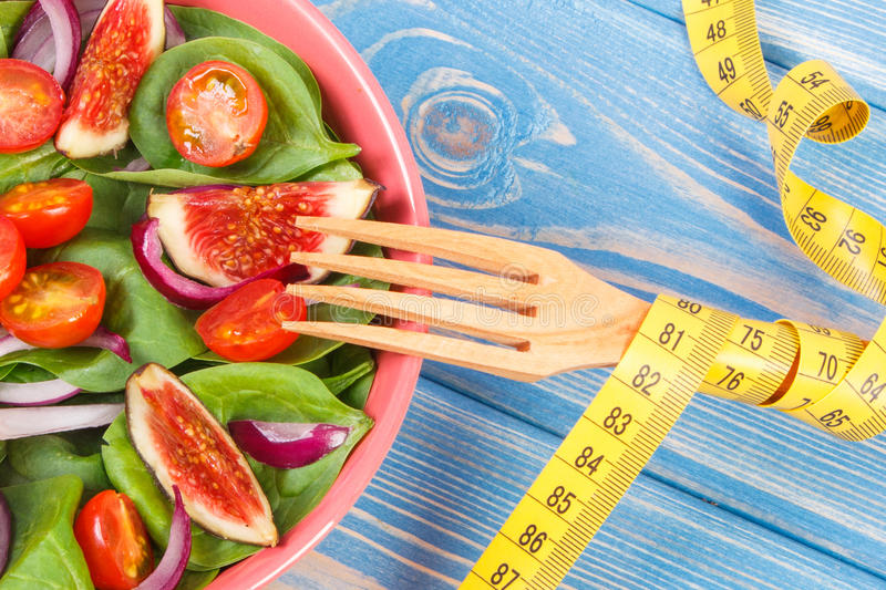 Fresh fruit and vegetable salad, fork with tape measure, healthy lifestyle, slimming and nutrition concept stock photos