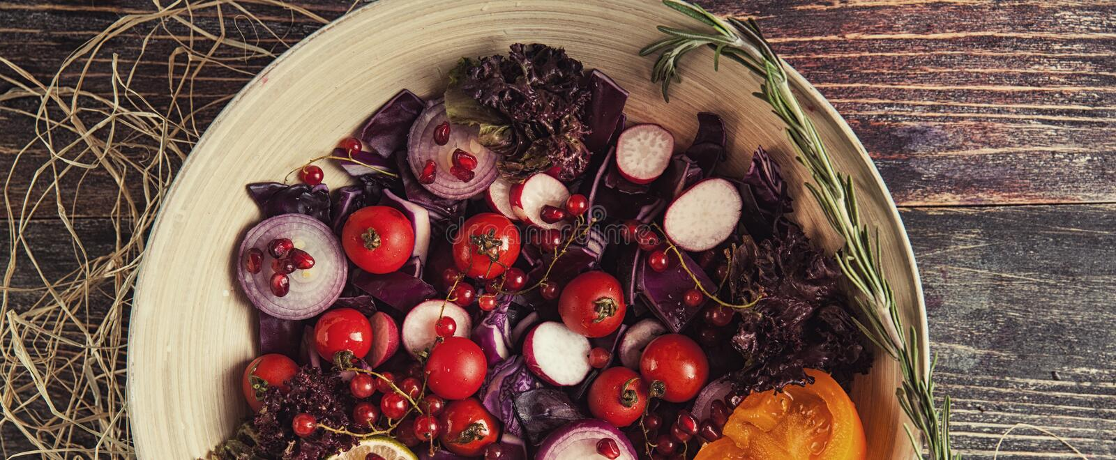 fresh fruit and vegetable salad in the plate or in bowl on wooden table with tomatoes, cabbage, pomegranate, lime, radish stock photography