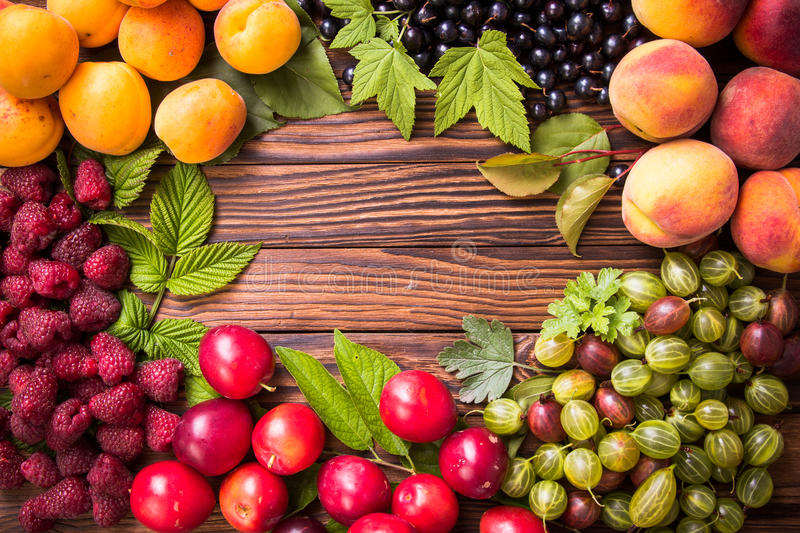 Fresh fruit on wooden table. Various fresh summer berries and fruits . Top view stock photos