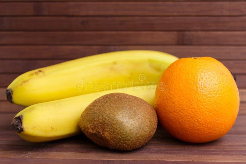 Fresh fruits banana, kiwi, orange isolated on wooden background. Healthy food. A mix of fresh fruit. Group of citrus fruits. Vegetarian raw fruit. Nutrition stock photography