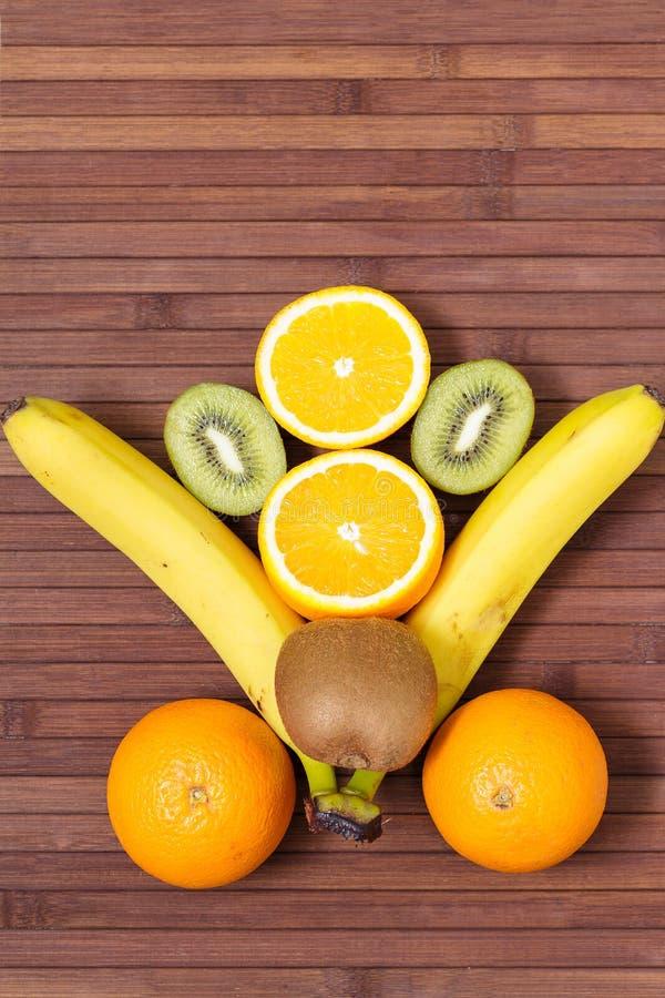 Fresh fruits banana, kiwi, orange isolated on wooden background. Healthy food. A mix of fresh fruit. Group of citrus fruits. Vegetarian raw fruit. Nutrition stock photo