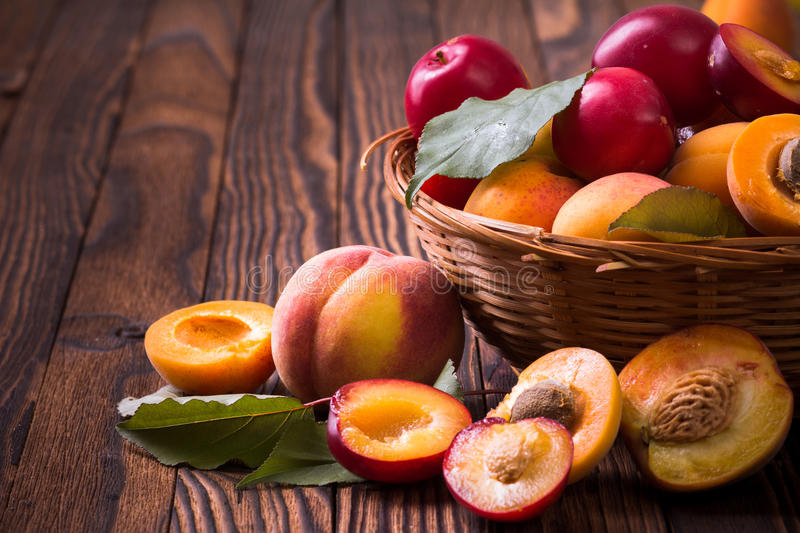 Fresh fruits in a basket. Whole and half peaches, plums and apricots in a basket royalty free stock images