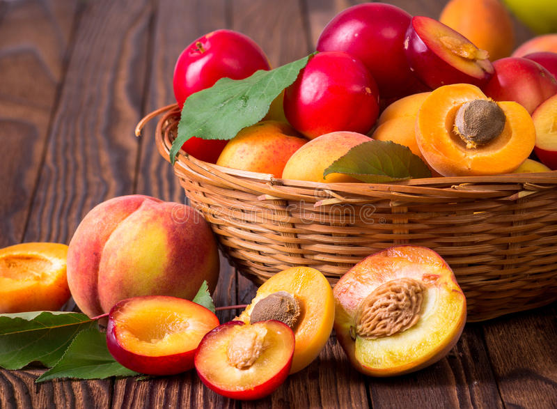 Fresh fruits in a basket. Whole and half peaches, plums and apricots in a basket royalty free stock photography
