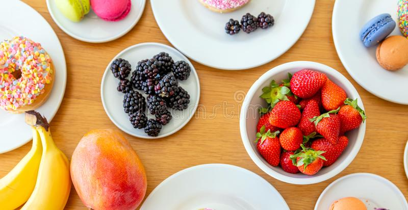 Colorful breakfast top view. Fresh fruits, donuts and macarons on wood. Banana, strawberry, blackberry and mango royalty free stock photo