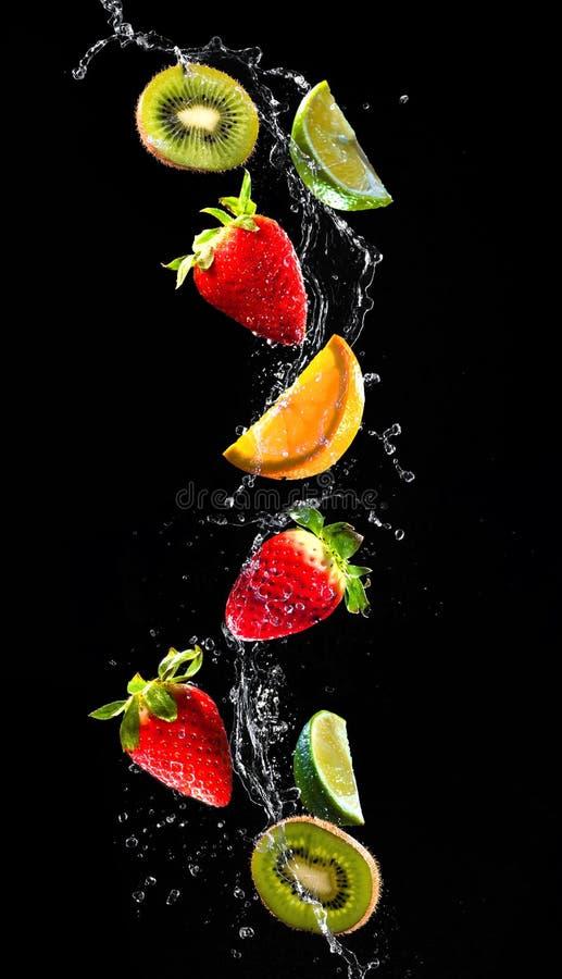 Fresh fruits falling in water splash royalty free stock image