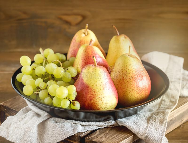 Fresh Fruits Green Grapes Pears Autumn Fruits Black Plate Wooden Background Horizontal Toned.  royalty free stock image