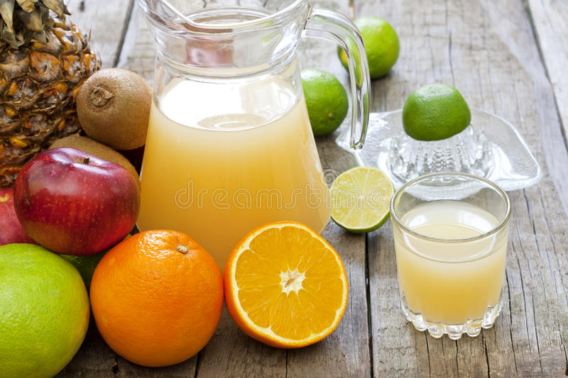 Fresh fruits juice with squeezer stock image