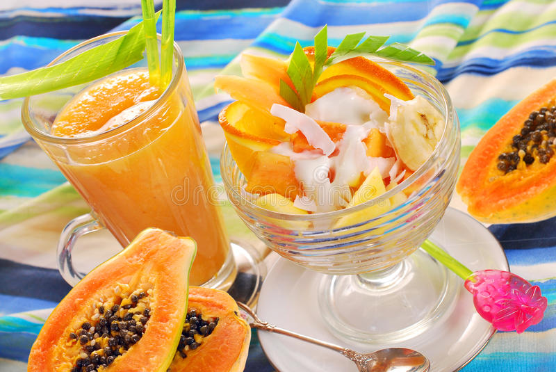 fresh fruits smoothie and salad with papaya,banana,orange,pineapple and coconut stock photo
