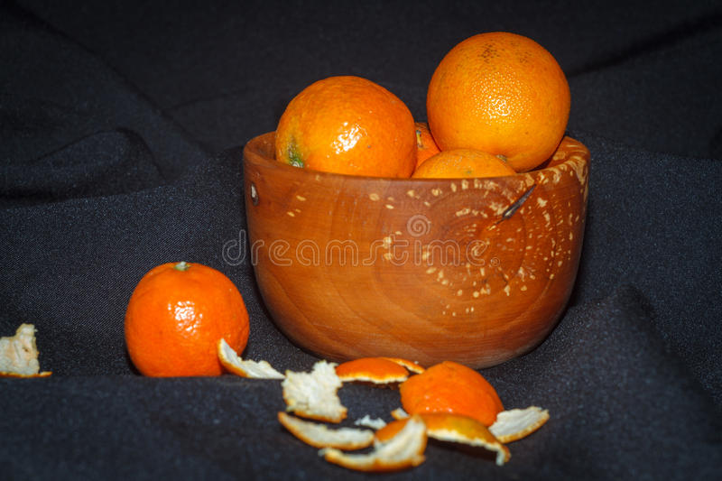 Fresh fruits tangerines in a wooden bowl stock image