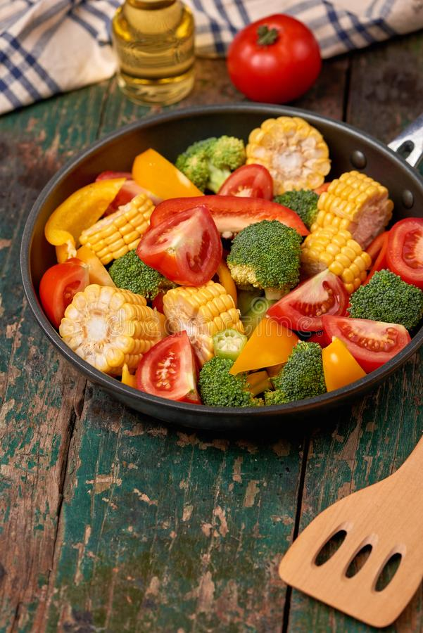 Fresh fruits and vegetables on a frying pan on an old wood background stock images