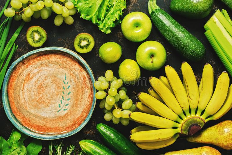 Fresh fruits and vegetables of green and yellow color, empty ceramic plate, flat lay. Space for text royalty free stock photo