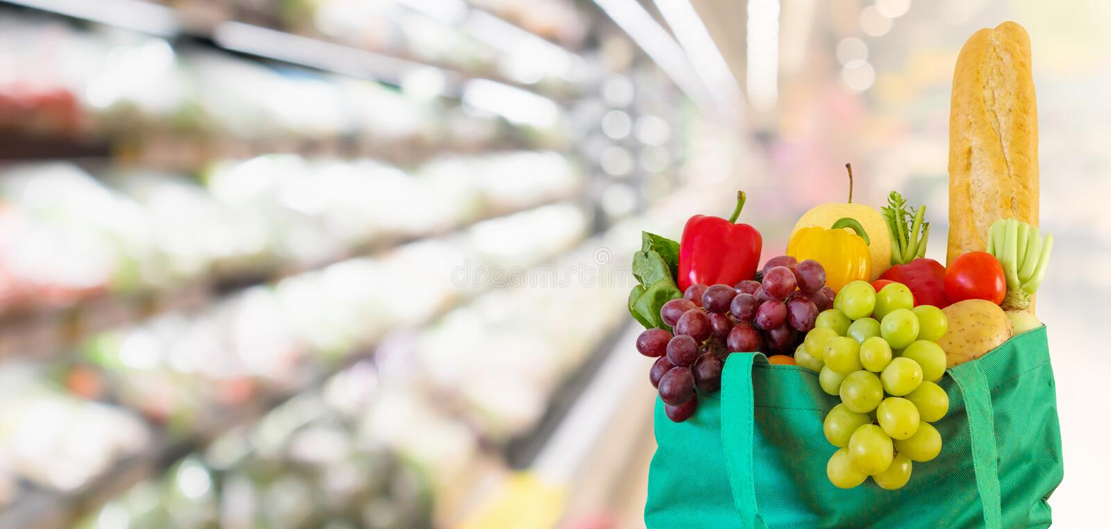Fresh fruits and vegetables in shopping bag with supermarket grocery store blurred defocused background royalty free stock photo