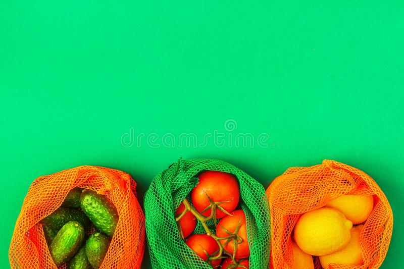 Fresh fruits and vegetables in reusable textile mesh bags royalty free stock image