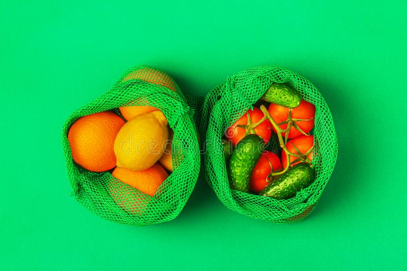 Fresh fruits and vegetables in reusable textile mesh bags stock image