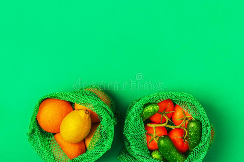 Fresh fruits and vegetables in reusable textile mesh bags royalty free stock photo