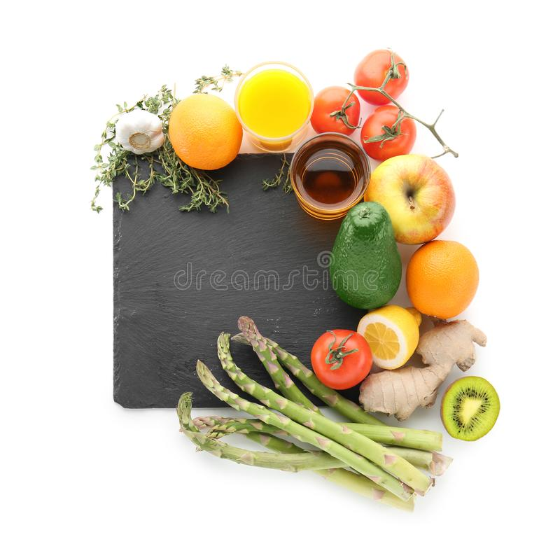 Fresh fruits and vegetables with slate plate on white background. Healthy food concept stock photo