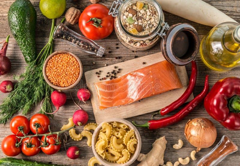 Fresh fruits and veggies, salmon, topshot. Variety of fresh fruits and veggies on the table, oats and spices, salmon fillet, topshot royalty free stock photos
