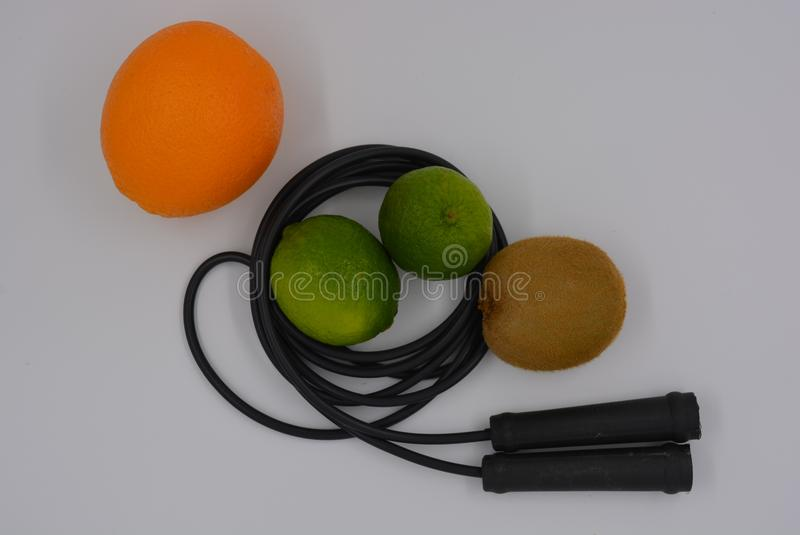 Sports black jump rope with two bright green limes, kiwi and orange orange on a white background, health and sport. stock photos