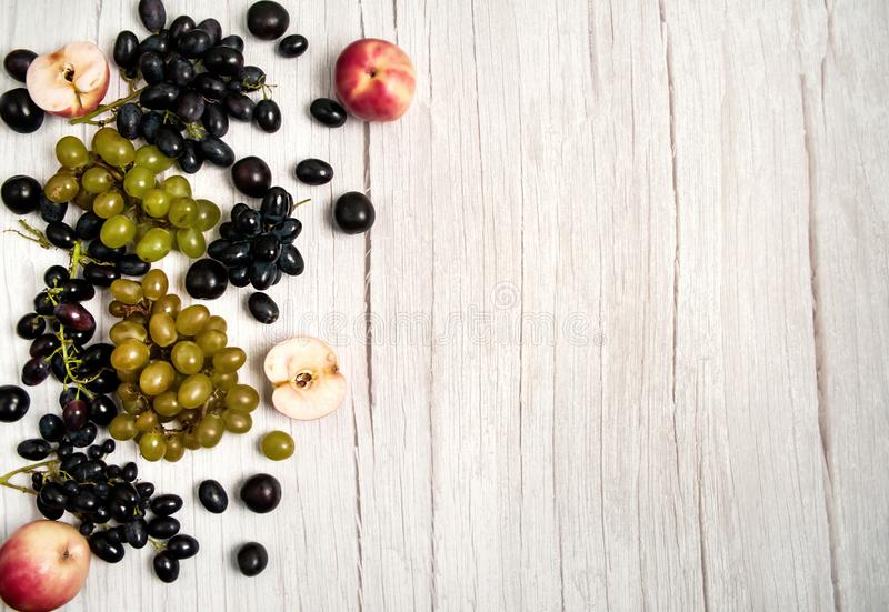 Red apples, prunes, black and green grapes. Fresh fruits on a white wooden background. Red apples, prunes, black and green grapes royalty free stock photo