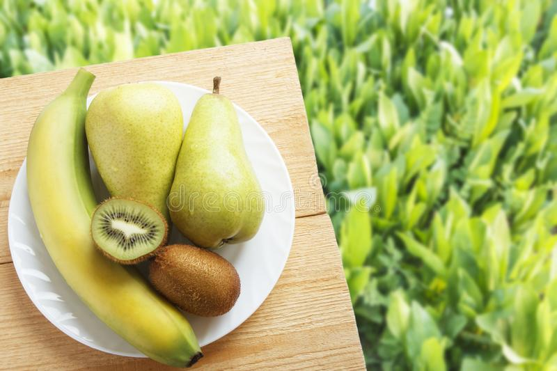 Fresh fruits on wooden table on background of green grasses. Healthy vegetarian food concept. Top view. Copy space.  stock images