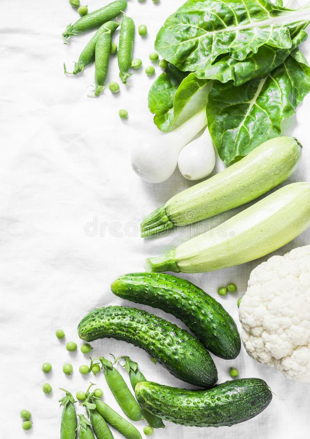 Fresh garden organic green vegetables - cucumbers, zucchini, chard, green peas, onions, cauliflower on a light background, top vie royalty free stock photography
