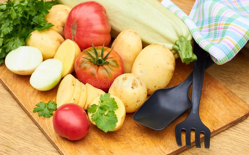 Fresh garden vegetables assorted o woodenn cutting board with kitchen stuff royalty free stock image