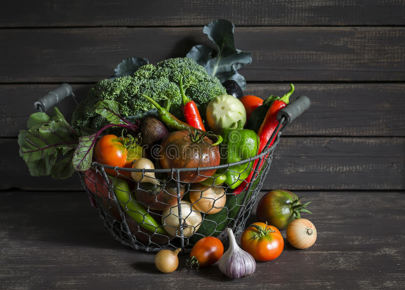 Fresh garden vegetables - broccoli, zucchini, eggplant, peppers, beets, tomatoes, onions, garlic - vintage metal basket stock photography