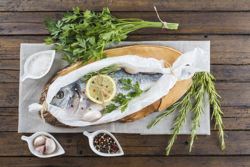 Fresh gilt-head sea bream ready to cook. Raw gilt-head sea bream with herbs and spices in a bakery release paper prepared to be cooked royalty free stock images