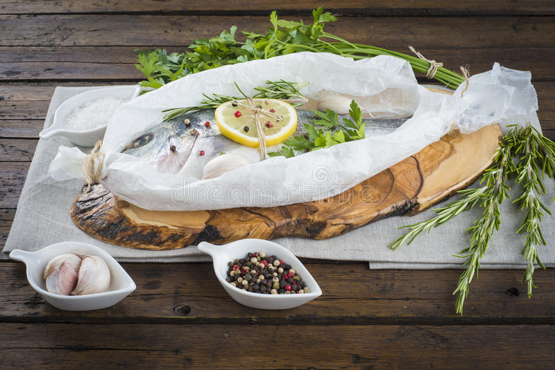 Fresh gilt-head sea bream ready to cook. Raw gilt-head sea bream with herbs and spices in a bakery release paper prepared to be cooked royalty free stock photography