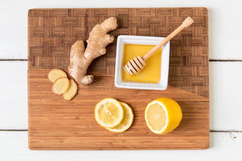 Fresh ginger root, lemon and honey on wooden cutting board royalty free stock image