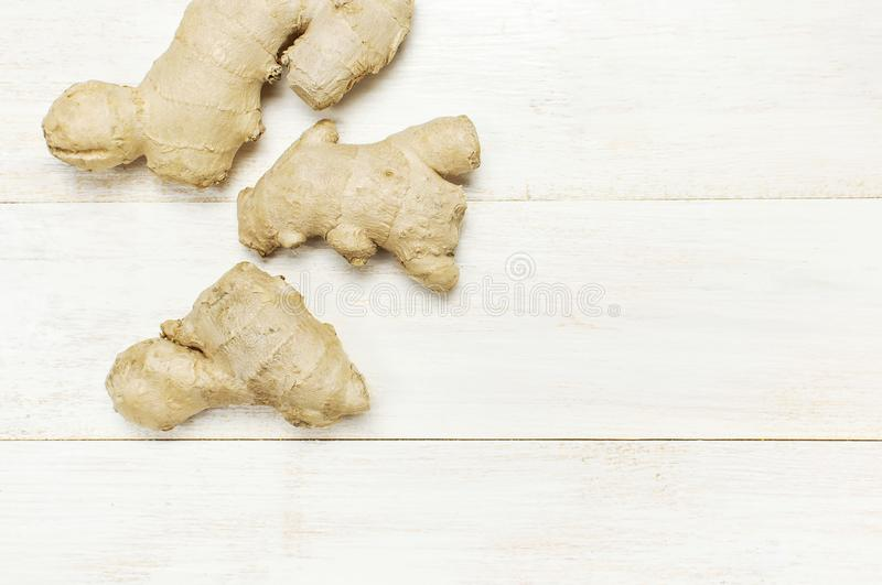 Fresh Ginger root on white wooden background top view with copy space. Minimalistic style, seasoning, spice, ingredient for tea. stock photography