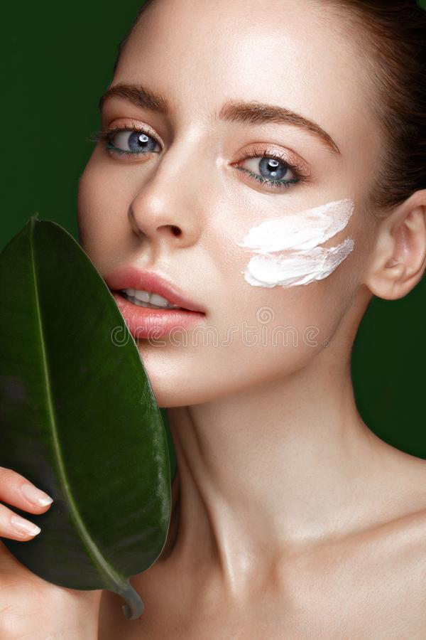 Fresh girl with cream on face. Beautiful fresh girl with cosmetic cream on the face, natural make-up and green leaves. Beauty face. Photo taken in the studio royalty free stock photography