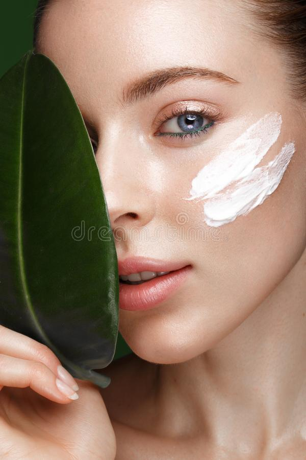 Fresh girl with cream on face. Beautiful fresh girl with cosmetic cream on the face, natural make-up and green leaves. Beauty face. Photo taken in the studio royalty free stock photo