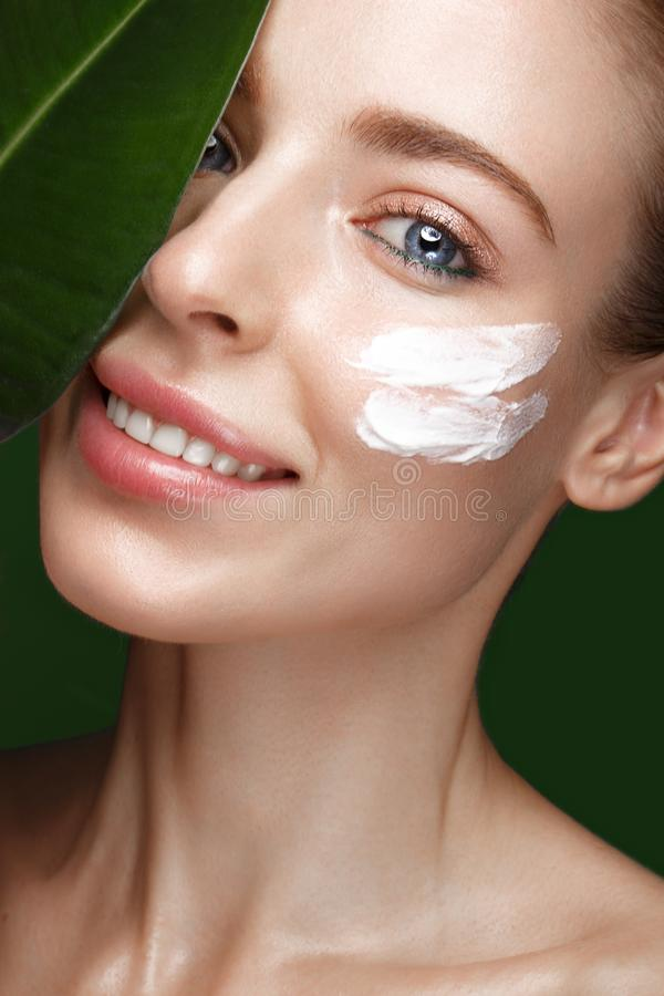 Fresh girl with cream on face. Beautiful fresh girl with cosmetic cream on the face, natural make-up and green leaves. Beauty face. Photo taken in the studio royalty free stock images