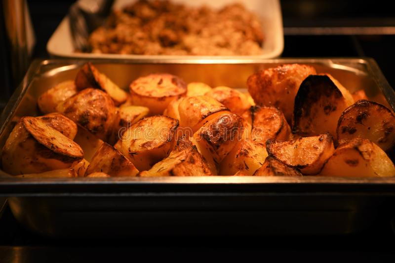 Delicious golden crispy cooked and served fresh vegetable of roast potatoes in a dish royalty free stock images