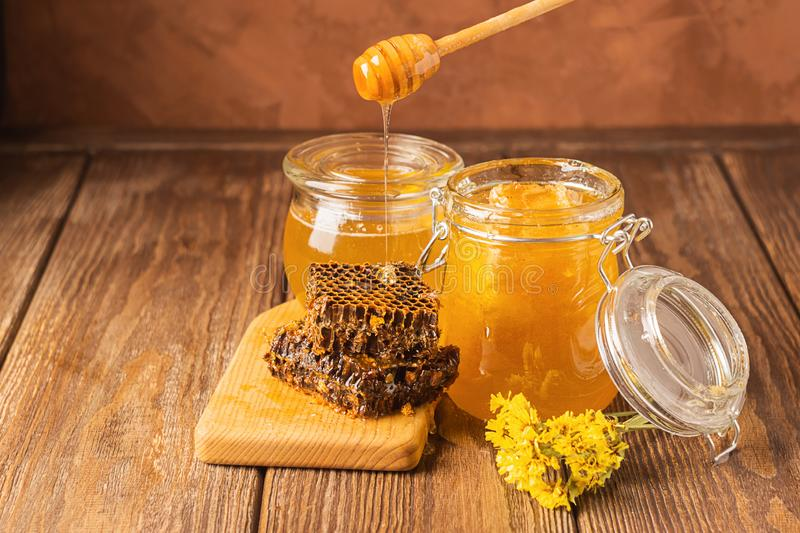 Fresh golden honey flows from a wooden spoon into a jar. Bee aromatic honey on a wooden background on the table. The concept of natural products. Horizontal royalty free stock photos