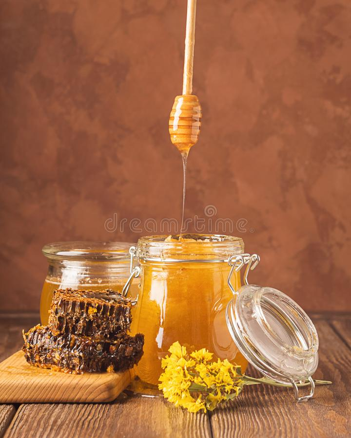 Fresh golden honey flows from a wooden spoon into a jar. Bee aromatic honey on a wooden background on the table. royalty free stock photo