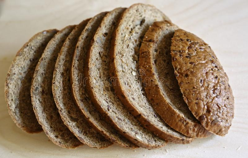 Fresh grain bread is cut exactly by pieces for food and sandwiches. Grain bread is cut on pieces exactly stock photo