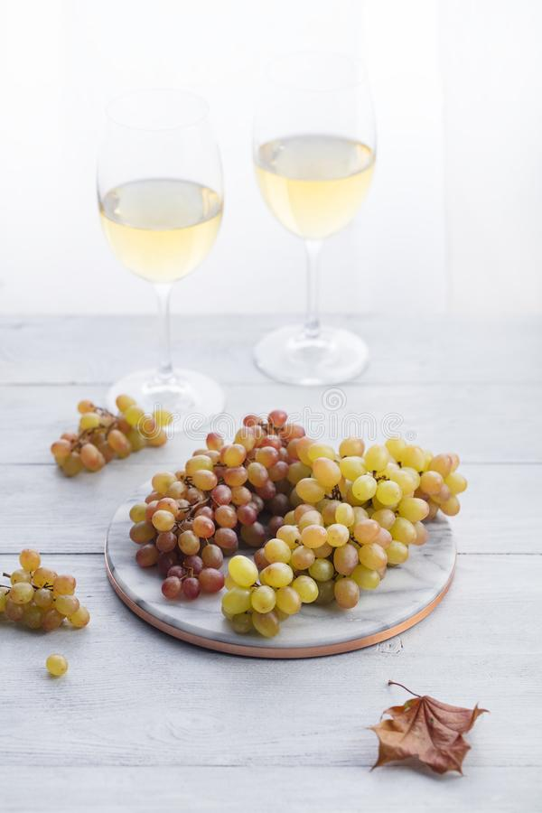 Fresh grape on marble board with glasses of wine. Wooden background. stock photography