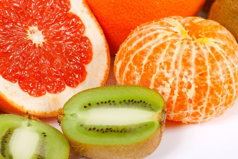Fresh grapefruit, tangerine and kiwi closeup stock images
