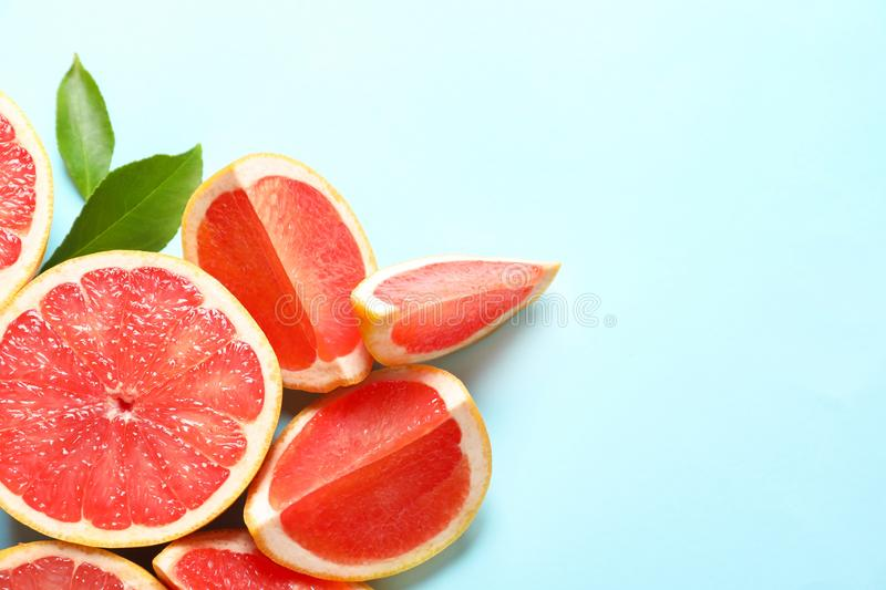 Fresh grapefruits and leaves on color background, flat lay. Citrus fruits. Fresh grapefruits and leaves on color background, flat lay with space for text. Citrus stock photography