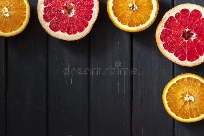 Fresh grapefruits and oranges on dark wooden background stock photo