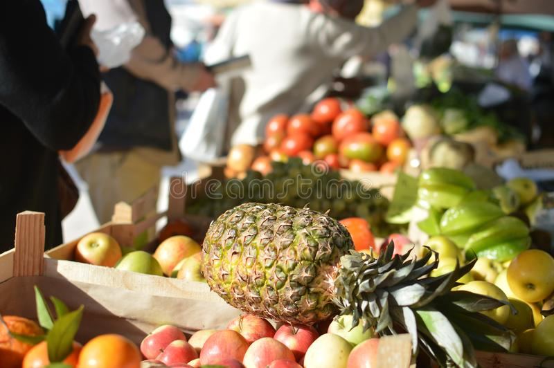Fresh grapes and pineapples on the grocery store in the supermarket. Fruit season. Vitamins and health royalty free stock image