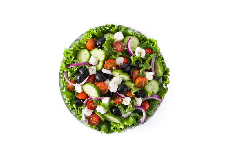 Fresh Greek salad in Plate with black olive,tomato,feta cheese, cucumber and onion isolated. On white background. Top view stock image