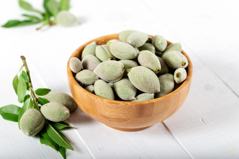 Fresh green almonds in a wooden bowl stock photo